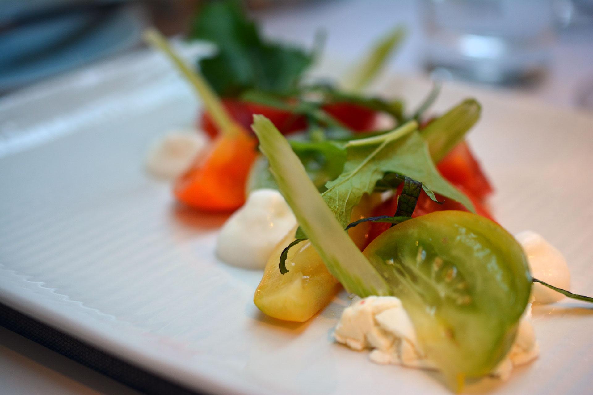 Paradeisvielfalt, roh mariniert und aufgeschlagen, geräucherter Ziegenkäse, Stangensellerie als Salat