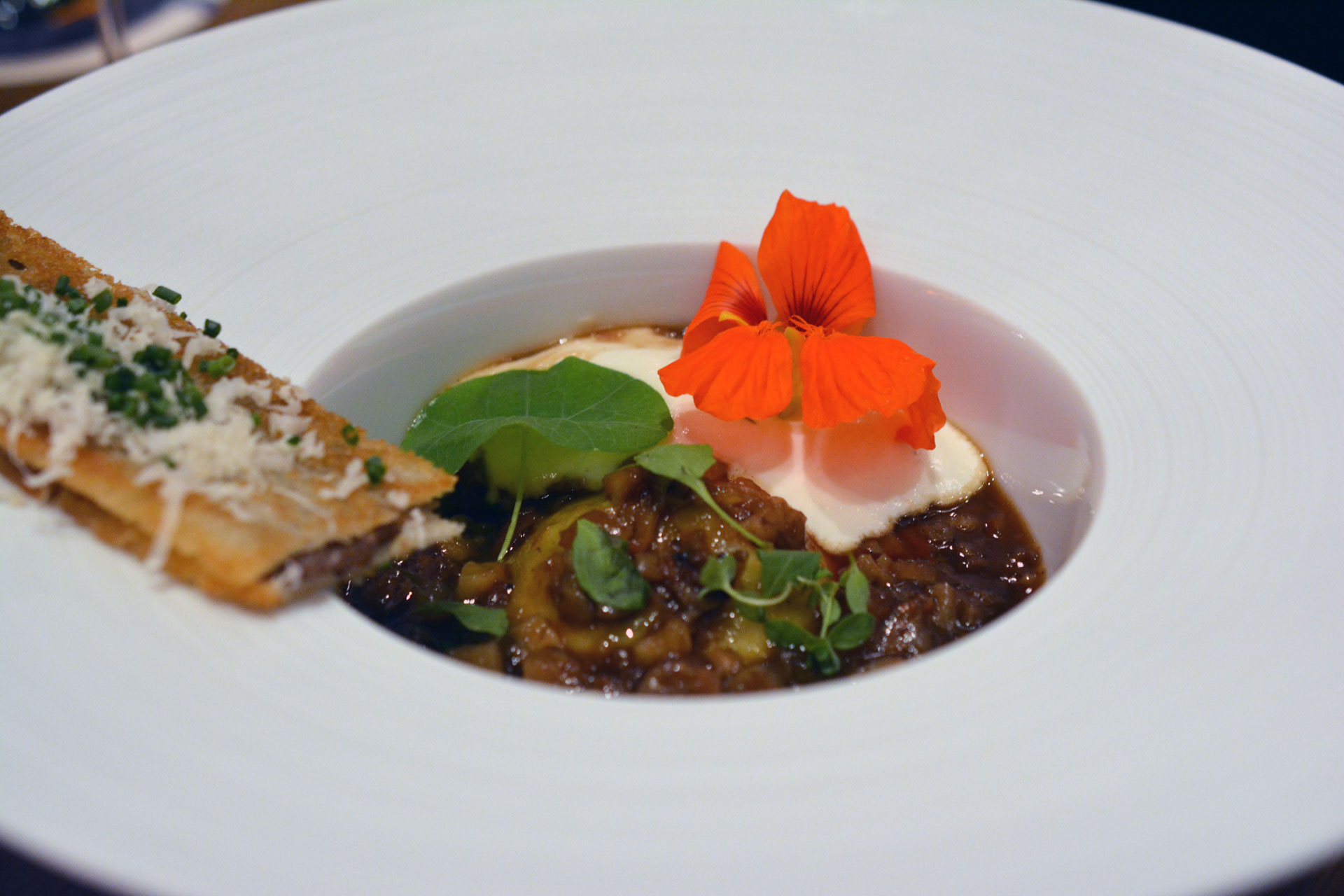 Ravioli gefüllt mit Shiitake-Pilzen, Ragout von Schweinfüssen, Baguette mit Schweinskopf, Estragonblüte, Espuma