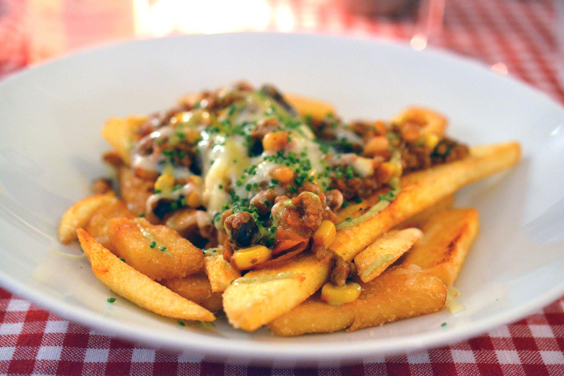 """We Love America: """"Chili Cheese Fries"""" - handgeschnitzte Pommes darauf hausgemachtes Rinder Chili con Carne mit Bohnen, Mais, Gruyère Käse"""