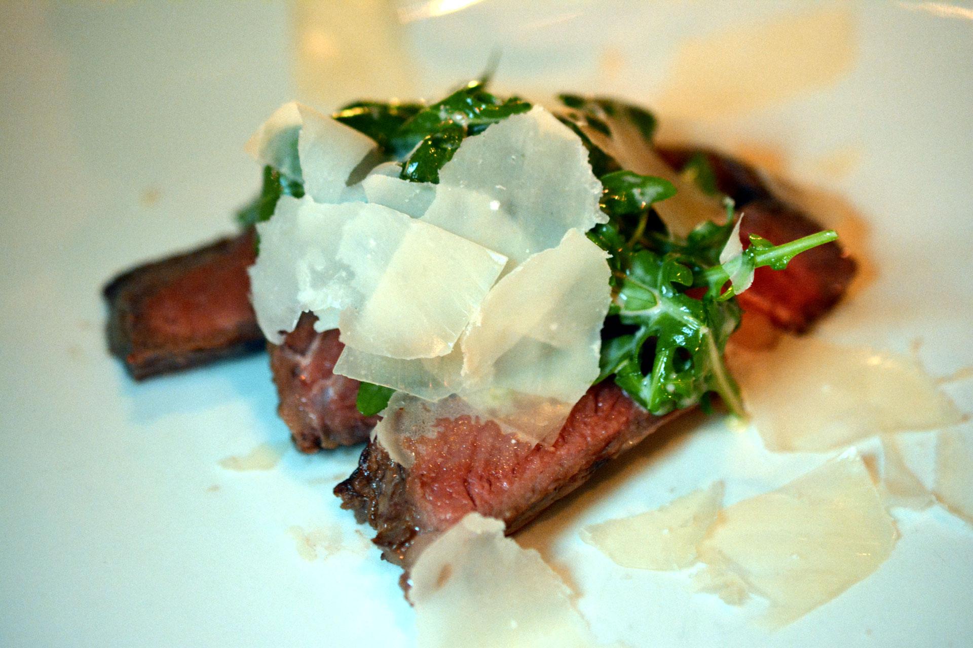 Dünn geschnittenes Rib Eye Steak mit Rucola und Parmesan